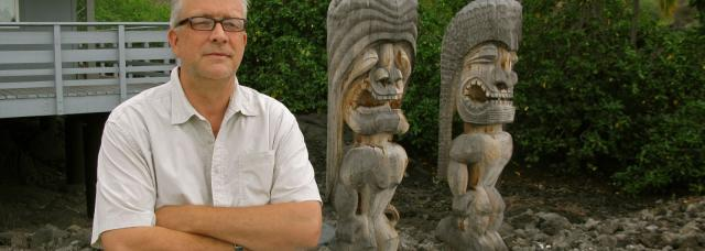Photo of Sven Kirsten with two carved tikis